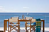 Esstisch aus Holz und Regiestühle auf Terrasse mit Glasbrüstung und Meerblick
