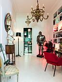 Büste auf Konsole unter Wandspiegel, Ritterausrüstung, Regal und Polsterstuhl am Tisch im Vorzimmer