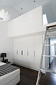 Weißer Einbauschrank, darüber Galerie mit Leiter in weißem Schlafzimmer