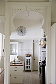 View through arched doorway into white country-house kitchen