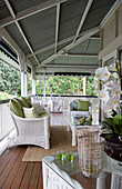 White rattan furniture with green cushions on veranda