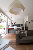 View past sofa into kitchen with counter and bar stools in open-plan interior