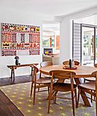 Holzstühle um runden Esstisch auf Teppich mit Ethnomuster
