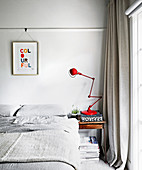 Red articulated lamp in the light gray bedroom