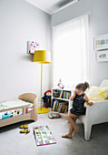 Girls in light gray children's room with yellow accents