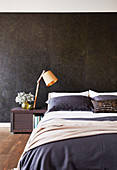 Black marble wall behind the bed in the bedroom