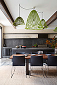 Green designer lights above the dining table in front of the open kitchen