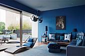 Blaues Wohnzimmer mit verschiedenen Sitzmöbeln und Liege vor Glasschiebetür