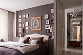 Gallery of photos on wall above double bed in taupe bedroom
