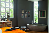Free-standing concrete bathtub in bathroom with grey walls decorated with framed record covers an, industrial window