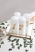 DIY Advent arrangement of candles and scattered decorations on mirrored tray