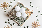 DIY Advent arrangement of candles, bauble, scattered decorations and straw stars on mirrored tray