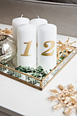 DIY Advent arrangement of candles, scattered decorations and straw stars on mirrored tray