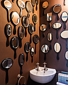 Ebony hand mirrors on wall of bathroom