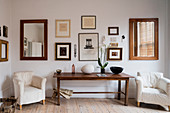 Orchidee and wooden bowl on farmhouse table flanked by pair of armchairs, assorted artwork and mirrors hang on the wall