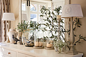 Table lamps, olive branches and glass vessels on sideboard