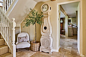 Antique longcase clock, olive tree and easy hair in stairwell