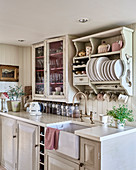 Plate rack and glass fronted cabinet above kitchen counter