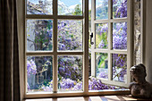 Vintage bust on windowsill with view of wisteria