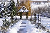 Frozen pond and pavilion in snowy garden