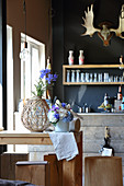 Vase of delphiniums and DIY flower arrangement with driftwood on kitchen table