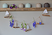 Handcrafted garland of paper boats and summer flowers