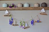 Selbstgebastelte Girlande aus Segelschiffchen und Sommerblüten