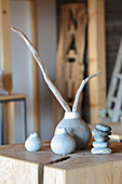 Pieces of driftwood in simple white-and-grey vases