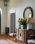 Old wooden Danish chest flanked by pair of Louis XVI chairs in hallway with restored pine floorboards and nickel plated lantern
