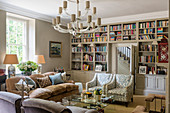 Murano chandelier and sofas and chairs in living room with inbuilt book shelves