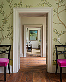 Wall paper around doorway flanked by pair of dining chairs upholstered in velvet