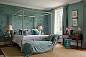 Silk wallpaper in elegant bedroom with four poster bed and sisal rug