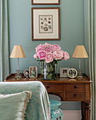 Pink peonies on antique dressing table with framed photos and small lamps