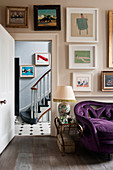 A purple sofa upholstered in velvet in living room with assorted artworks