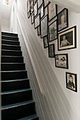Framed black and white photos on wall along staircase