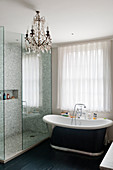 Roll-top bath in bathroom with mosaic tiles and glass chandelier