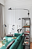 Turquoise velvet sofa in seating area and partition shelving in small apartment