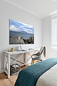 Seascape on wall above console table in bedroom