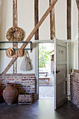 Open front door in converted barn with brick wall base