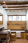 Badewanne mit Holzverkleidung unterm Fenster im rustikalen Bad