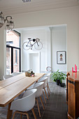 Shell chairs at wooden table in dining room with bicycle hung on wall