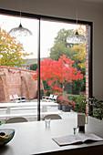 Blick von der Kücheninsel durch die Fensterfront auf den Innenhofgarten