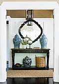 Console table with Asian vases against a cassette wall