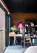 Desk by the window against a wall with wood paneling