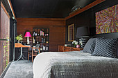 Bedroom in gray, black and brown with wooden paneling