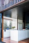 View through an open patio door into the modern, minimalist kitchen