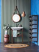 Waschtischständer und runder Spiegel an Wellblechpaneel, seitlich Metallregal mit Schulbaden an blauer Wand