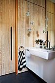 Waschtisch und Wandpsiegel im Badezimmer mit Holzverkleidung