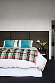 Double bed with colorful bedspread in the bedroom