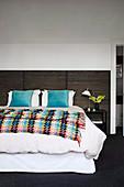 Doppelbett mit bunter Tagesdecke im Schlafzimmer